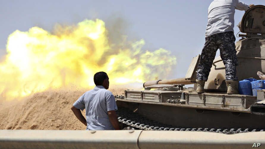 A tank belonging to the Western Shield, a branch of the Libya Shield forces, fires during a clash with rival militias around the former Libyan army camp, Camp 27, in the 27 district, west of Tripoli, Aug. 22, 2014.