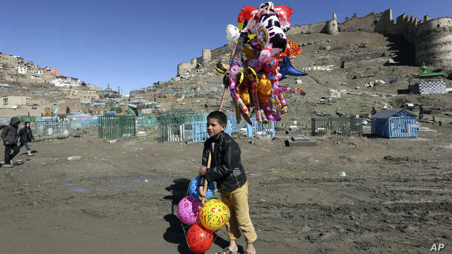 A young boy sells balloons in Kabul, March 23, 2017. An aid group said Thursday that nearly a third of all children in war-torn Afghanistan are unable to attend school, leaving them at increased risk of child labor, recruitment by armed groups, early...