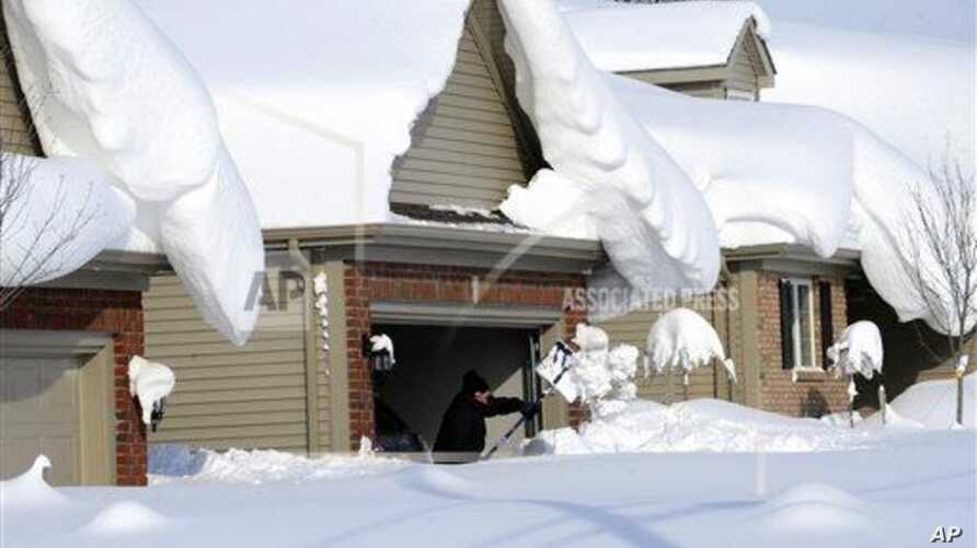 Man tries to dig out his driveway on Bowen Road in Lancaster, New York, Nov. 19, 2014.