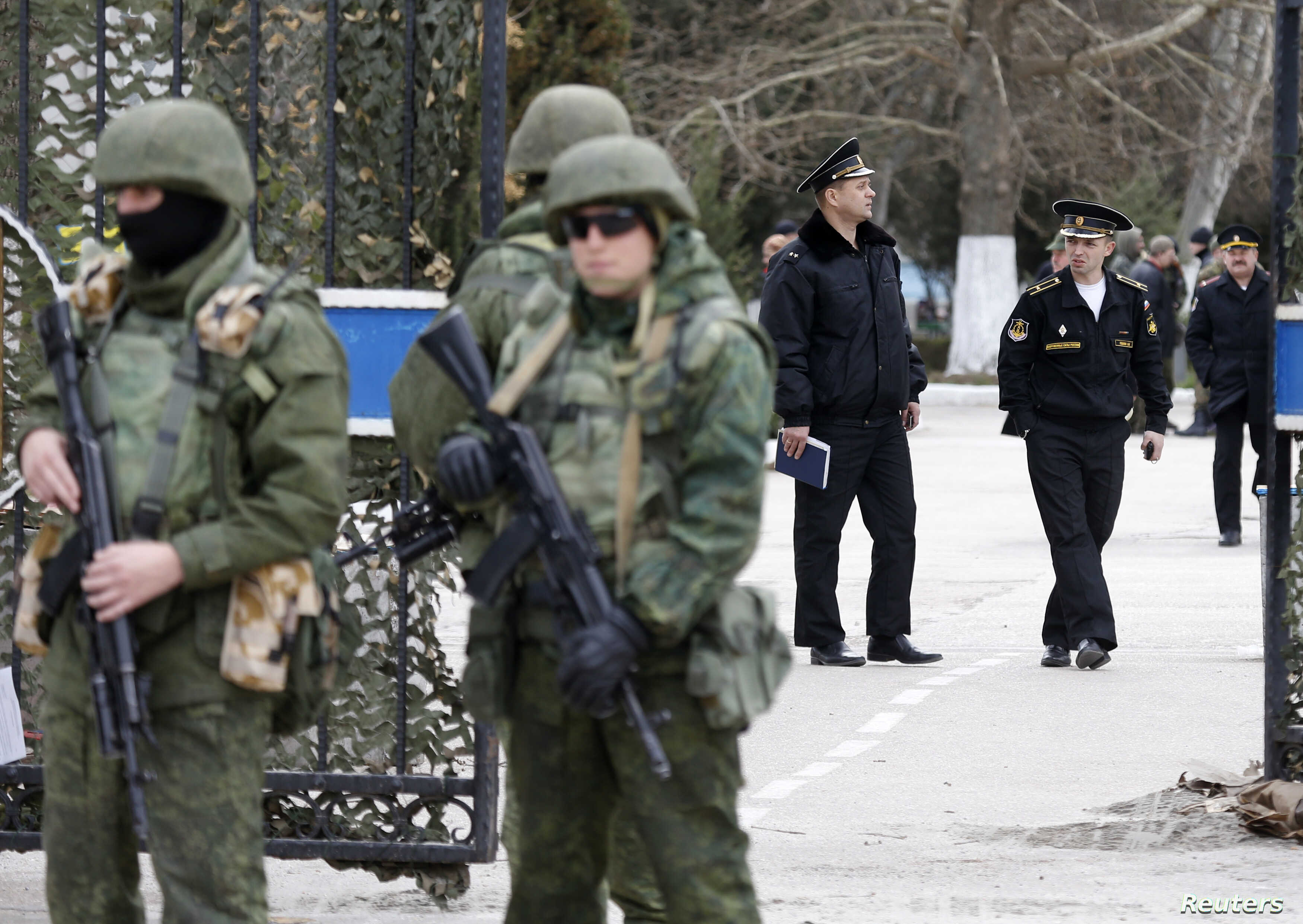 Armed men (L), believed to be Russian servicemen, stand guard outside Ukraine's naval headquarters after it was taken over by pro-Russian forces, as Russian naval officers (R) are seen in the background, in Sevastopol, March 19, 2014.