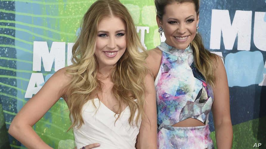 FILE - Tae Dye, right, and Maddie Marlow, of the musical group Maddie & Tae, arrive at the CMT Music Awards in Nashville, Tennessee, June 10, 2015.