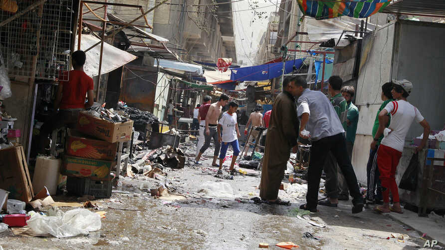 Civilians inspect the site of a bomb attack in Shorja Market in Baghdad, Iraq, July 17, 2014.
