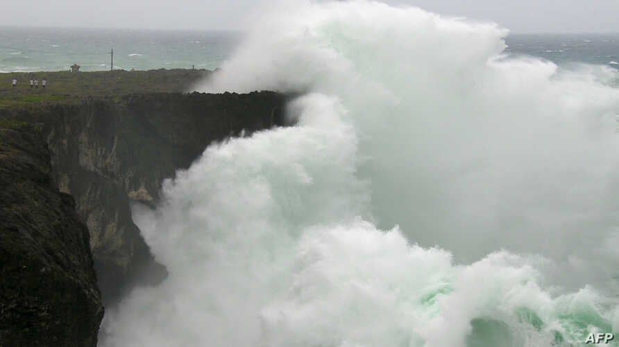 Large waves created by Typhoon Vongfong crash into a cliff wall along the coast of Okinawa, Oct. 13, 2014.