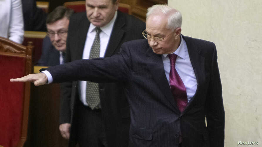 Ukranian Prime Minister Mykola Azarov (R) gestures during a session of the Parliament in Kyiv, Dec. 3, 2013.