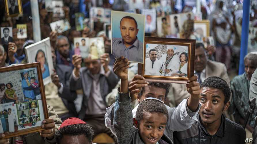 Members of Ethiopia's Jewish community hold pictures of their relatives in Israel, during a solidarity event at the synagogue in Addis Ababa, Ethiopia, Feb. 28, 2018.