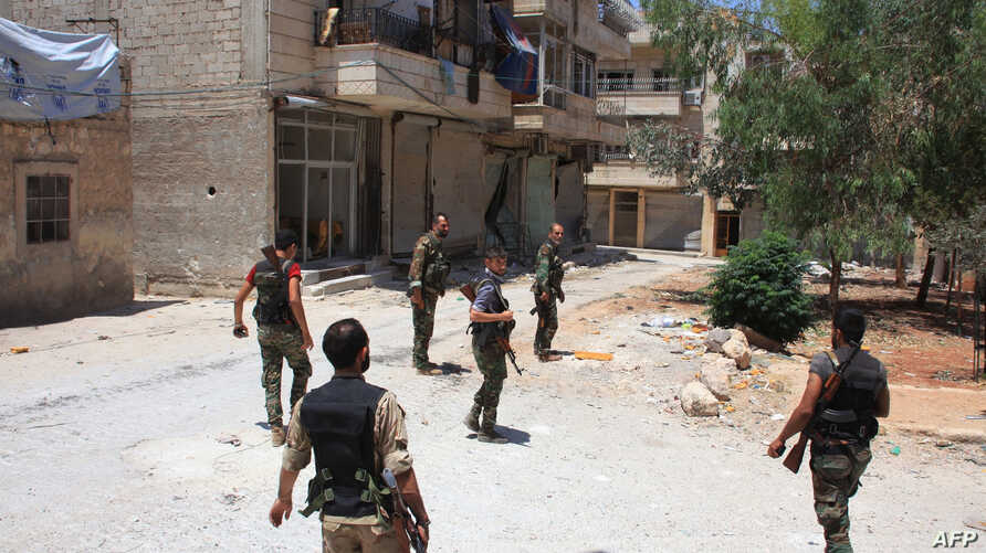 FILE - Syrian army soldiers patrol a street in government-controlled Aleppo's al-Khalidiya area where the army progressed towards the industrial zone of al-Layramoun and Bani Zeid on June 28, 2016.