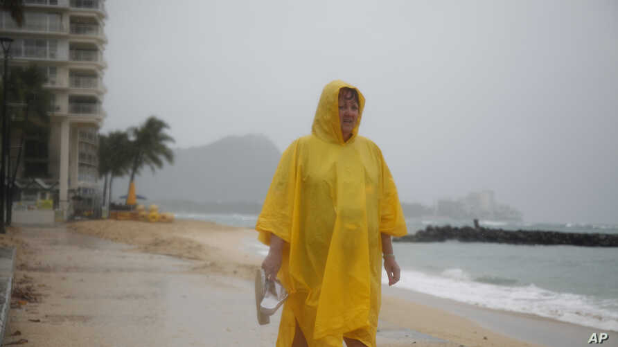 FILE - Maryanne Fisher, of League City, Texas, stands in the rain, Oct. 19, 2014, on Waikiki Beach with Diamond Head in the background in Honolulu as Hurricane Ana brought a steady rain to the Hawaiian Island of Oahu. On Wednesday, NOAA's Central Pac