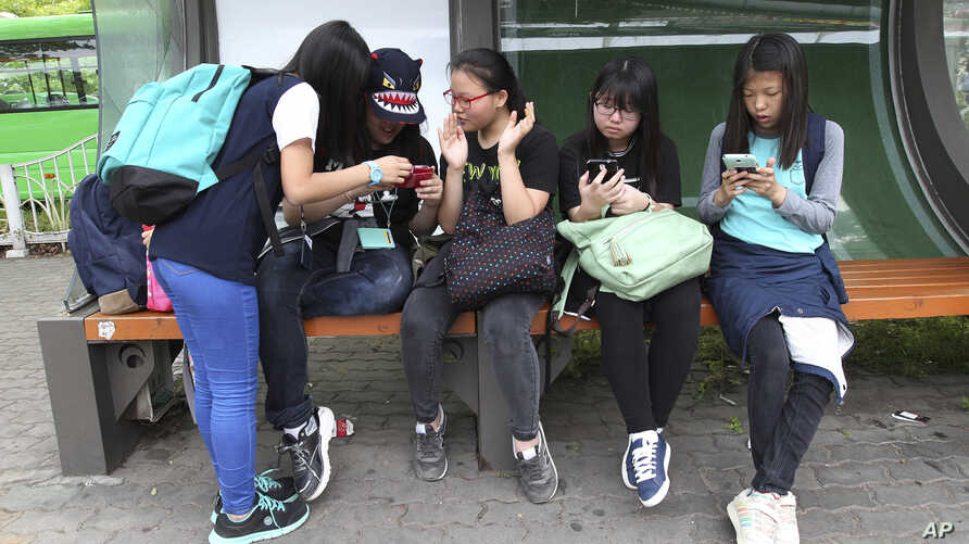 South Korean middle school students use their smartphones at a bus station in Seoul, South Korea, May 15, 2015.