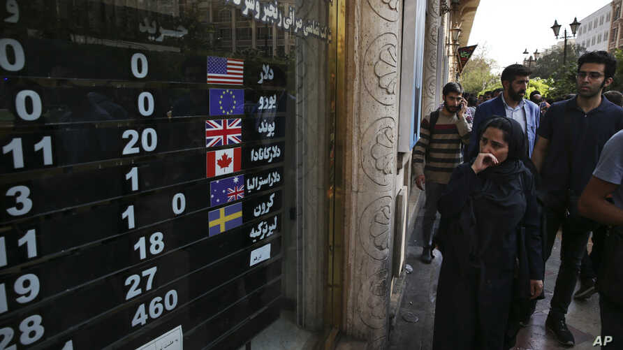 FILE - An exchange shop displays rates for various currencies, in downtown Tehran, Iran, Oct. 2, 2018. A battle is brewing between the Trump administration and some of the president's biggest supporters in Congress who are concerned that sanctions ...