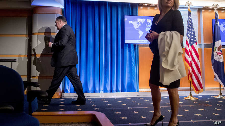 FILE - Secretary of State Mike Pompeo (L) and State Department spokeswoman Heather Nauert (R) depart a news conference at the State Department in Washington, Oct. 23, 2018.