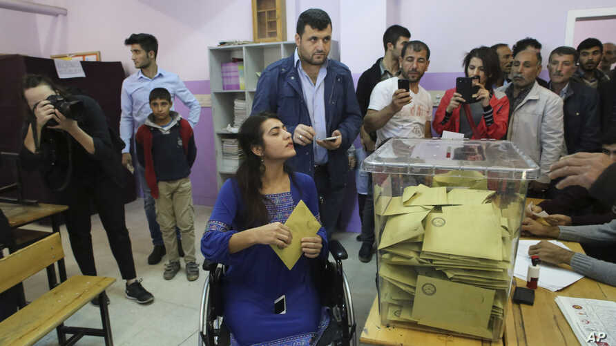 FILE - Using a wheelchair, Lisa Calan, who lost both her legs at an explosion June 5, 2015, in Diyarbakir, in Turkey's predominantly Kurdish southeast during a pro-Kurdish Peoples' Democratic Party'S, (HDP) rally for the previous elections, casts her