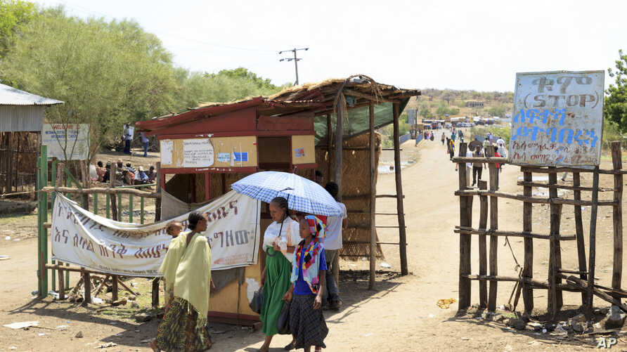FILE - People walk past a checkpoint in northwestern Ethiopia next to the border with Sudan, June 3, 2015. Sudan and Ethiopia agreed Tuesday to deploy joint forces to secure their border.