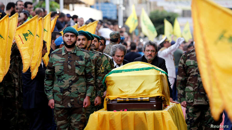 Brothers of top Hezbollah commander Mustafa Badreddine, who was killed in an attack in Syria, mourn over his coffin during his funeral in Beirut's southern suburbs, Lebanon, May 13, 2016