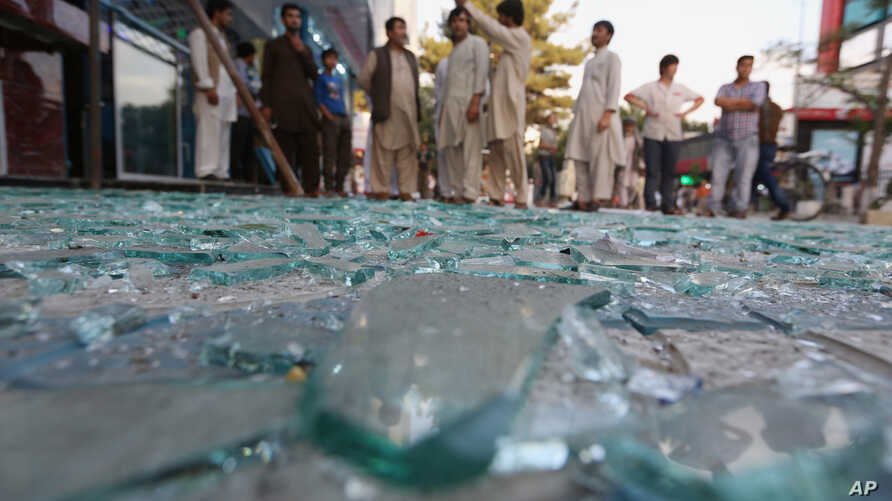 After a bomb explodes in a central business district of Kabul, Afghanistan, onlookers gather at the scene, July 13, 2015.
