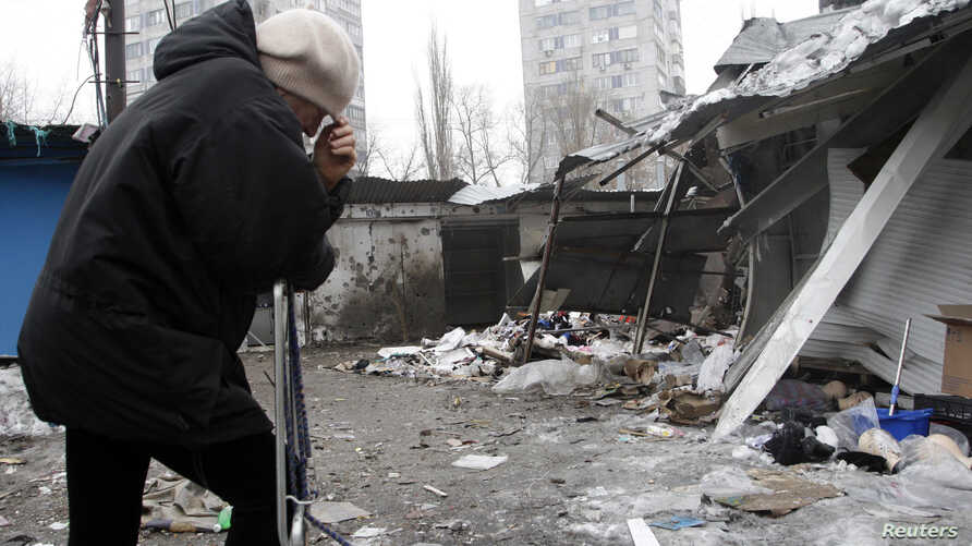 A woman reacts as she stands at a market that, according to locals, was recently damaged by shelling, in Donetsk, eastern Ukraine, Jan. 19, 2015.