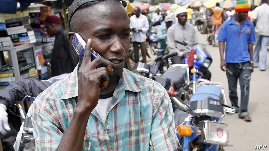 A motorcyclist phones sat on his motorbike on August 18, 2008 in Obalende, a district of Lagos.