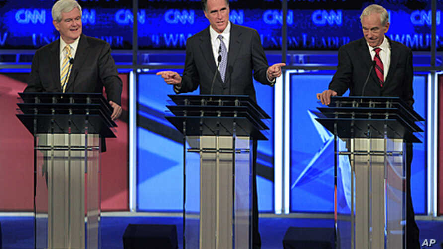 Former Massachusetts Governor Mitt Romney answers a question as former House Speaker Newt Gingrich, left, and Rep. Ron Paul, listen during the first Republican presidential debate in Manchester, New Hampshire, June 13, 2011