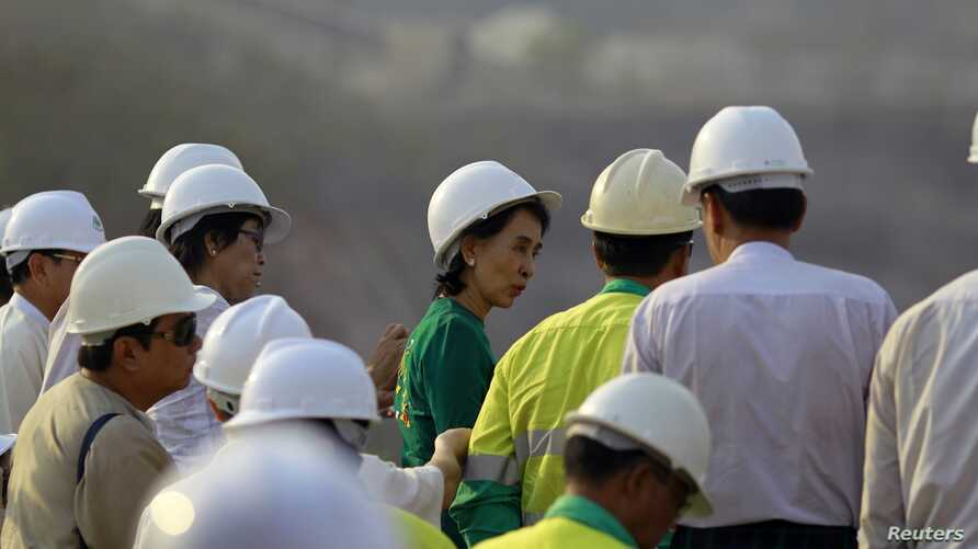 Burma pro-democracy leader Aung San Suu Kyi observes copper mine after meeting with villagers whose land was seized, Sarlingyi township, March 14, 2013.
