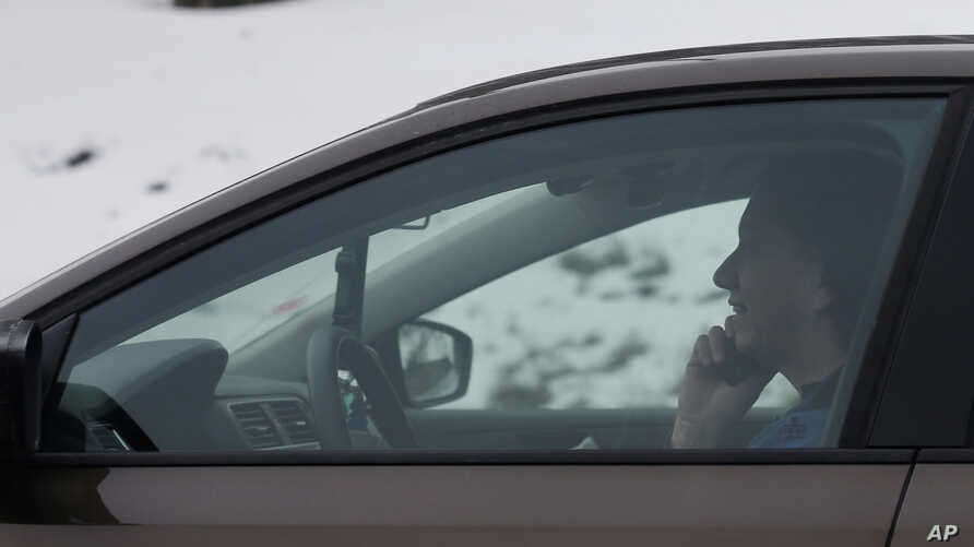 FILE -A motorist talks on a cell phone while driving on an expressway in Chicago, Dec. 19, 2013.