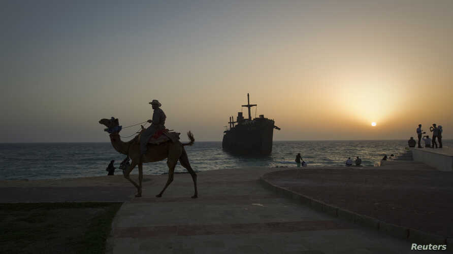 A man rides his camel along the coast, in front of the beached Greek ship Moula F, during sunset off Kish Island, 1,250 km (777 miles) south of Tehran, April 27, 2011.