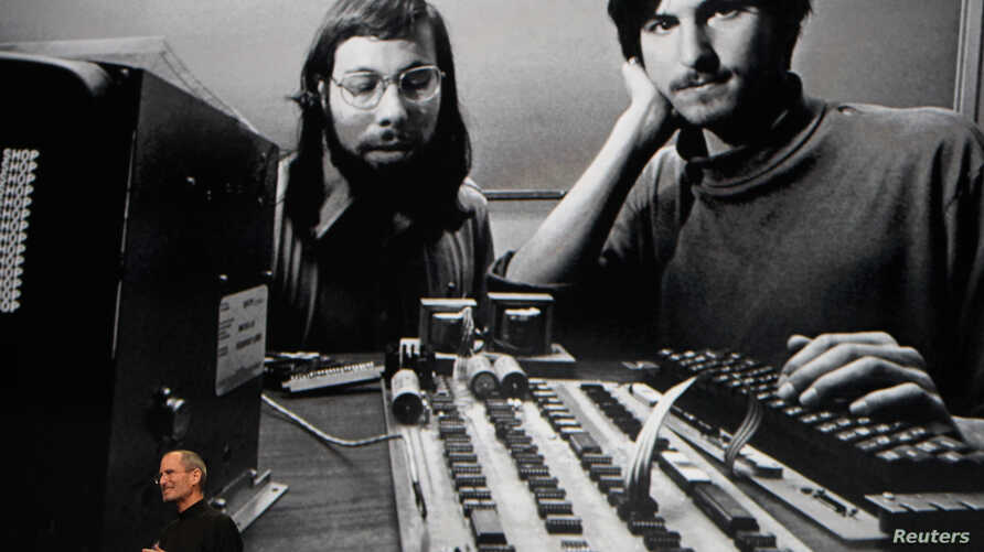 """Apple Chief Executive Officer Steve Jobs stands beneath a photograph of him and Apple-co founder Steve Wozniak from the early days of Apple during the launch of Apple's new """"iPad"""" tablet computing device in San Francisco, California, January 27, 2010"""