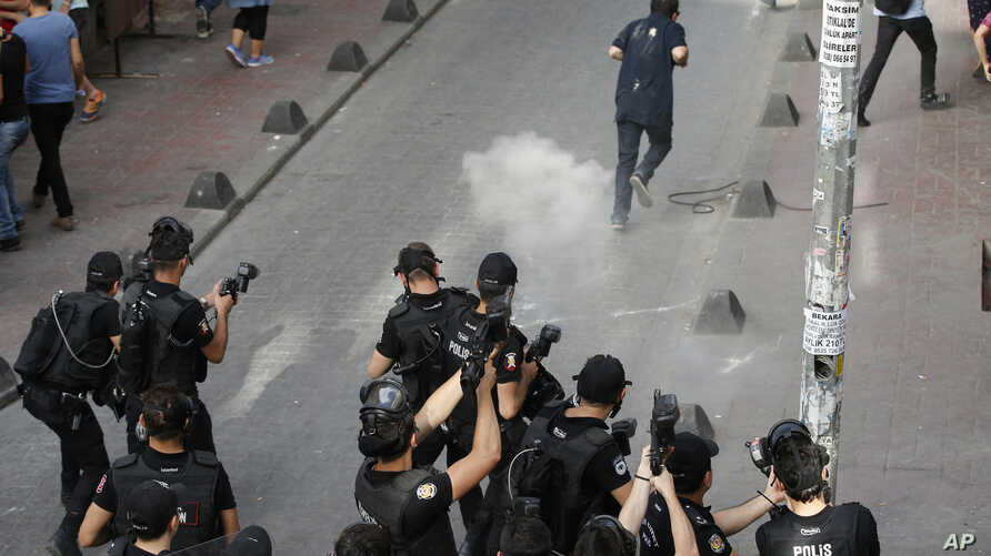 Turkish police officers fire tear gas and rubber bullets to disperse demonstrators who gathered for a gay pride rally despite a government ban, off Istiklal Avenue, central Istanbul's main shopping road, Sunday, June 19, 2016.