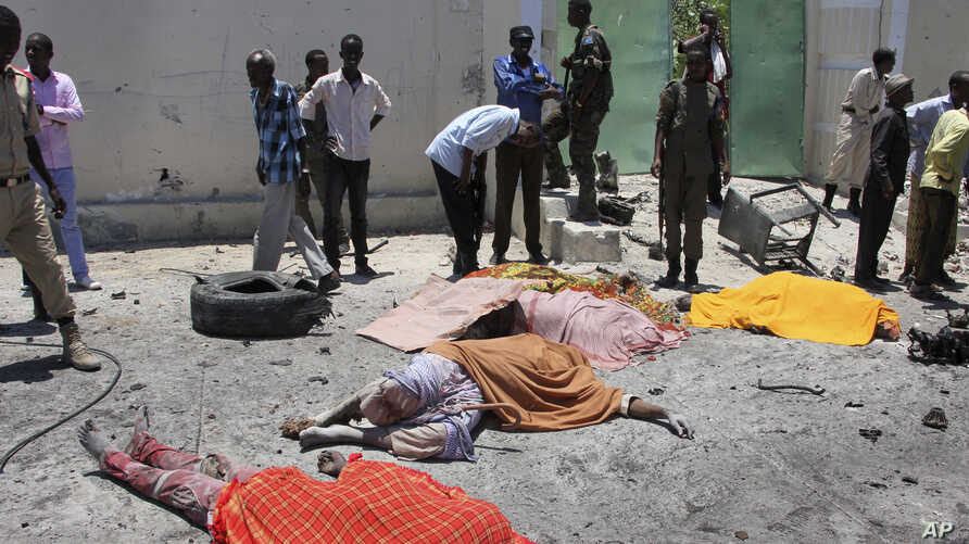 Somalis stand next to the bodies of civilians who were killed in a car bomb attack on a restaurant in Mogadishu, April 5, 2017.