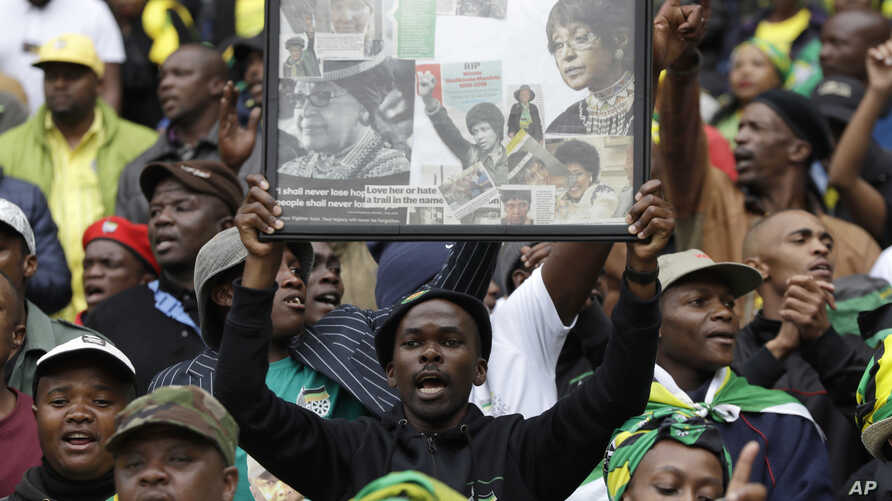 A man holds up a frame showing newspaper clippings of anti-apartheid activist Winnie Madikizela-Mandela during her memorial service at Orlando, Stadium, in Soweto, Apr. 11, 2018.