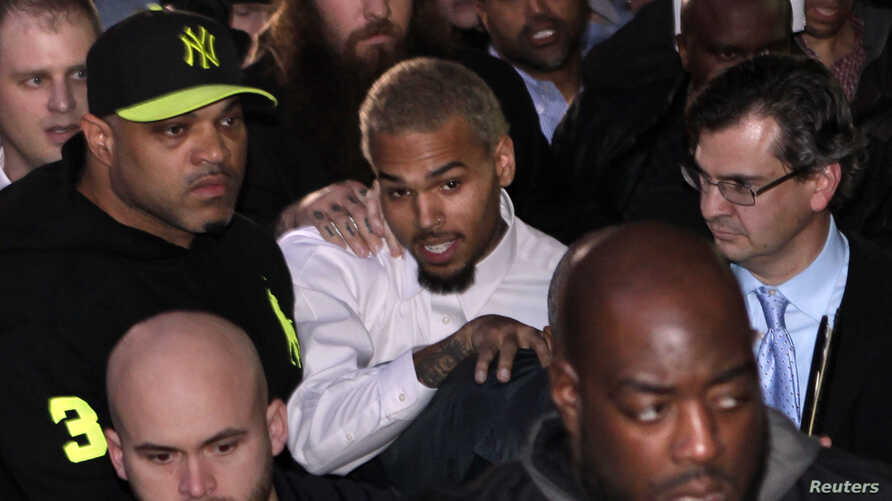 Singer Chris Brown (C) leaves the U.S. District Court in Washington, Oct. 28, 2013.