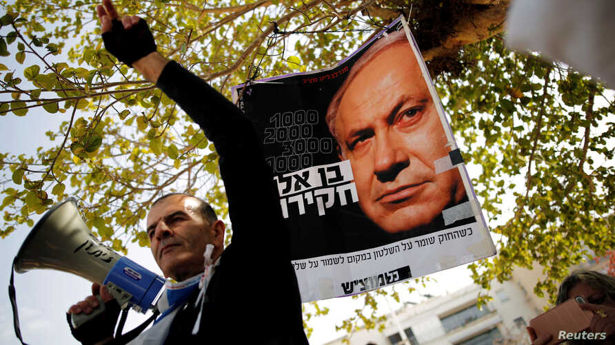 Protesters hold signs as they take part in a rally calling upon Israeli Prime Minister Benjamin Netanyahu to step down in Tel Aviv, Israel,  Feb. 16, 2018.