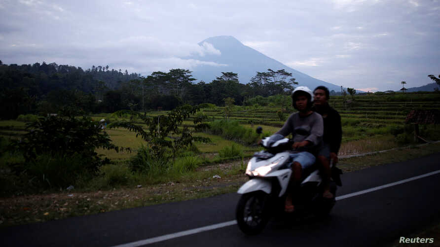 People ride a motorcycle past Mount Agung in the background, a volcano on the highest alert level, in Karangasem Regency, on the resort island of Bali, Indonesia, Sept. 24, 2017.