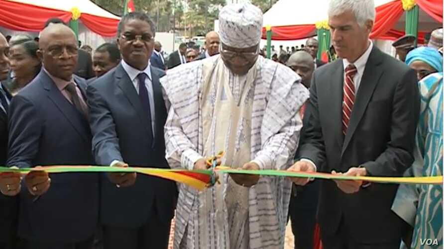 Cameroonian Prime Minister Philemon Yang cuts the symbolic ribbon at the inauguration of the Public Health Emergency Operations Center, in Yaounde, Cameroon, Dec. 3, 2018. (M. Kindzeka/VOA)