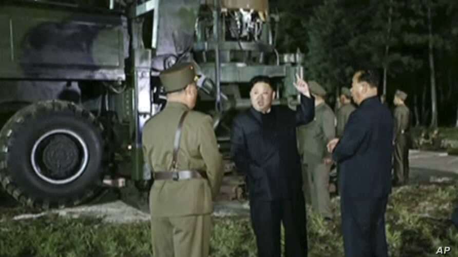 In this image made from video by North Korea's KRT, July 28, 2017, North Korean leader Kim Jong Un gestures at the site of a missile test at an undisclosed location in North Korea.