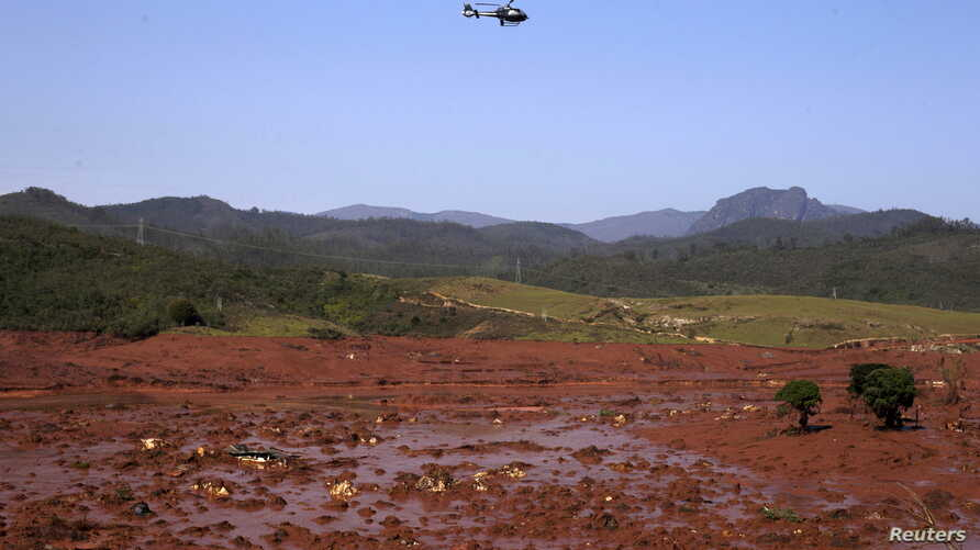 A helicopter flies over the Bento Rodrigues district, covered with mud after a dam owned by Vale SA and BHP Billiton Ltd burst in Mariana, Brazil, Nov. 6, 2015.