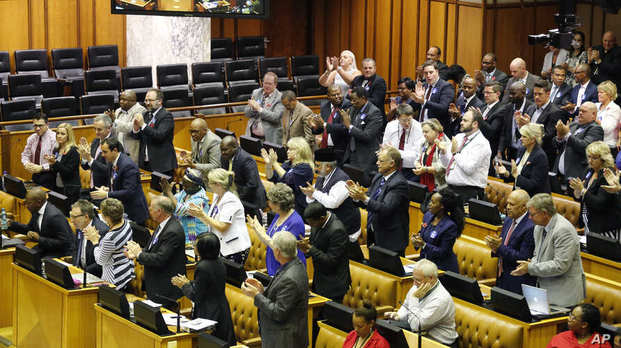 South Africa President's Scandals: South African DA, Democratic Alliance party leader, Mmusi Maimane, far left, is applauded by his party members after he spoke and called for a motion to remove South African President Jacob Zuma as President at Parl