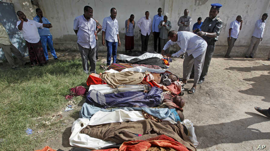 People observe bodies brought to Mogadishu after a number of civilians were killed during a raid by foreign and Somali forces in Barire village in southern Somalia.