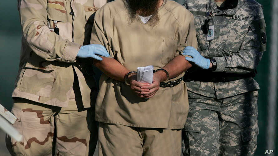 FILE - A shackled detainee is being escorted away from an Administrative Review Board hearing, at Camp Delta detention center at the Guantanamo Bay U.S. Naval Base in Cuba, Dec. 6, 2006.