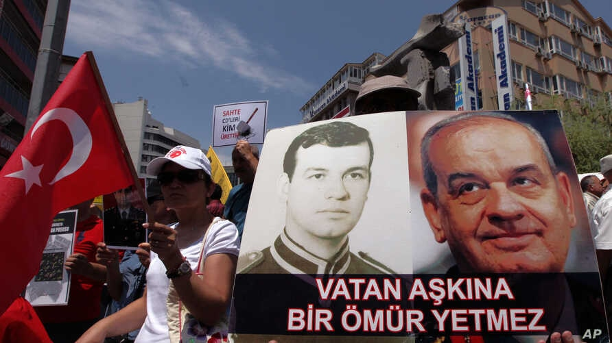 FILE - A person holds photos of Ilker Basbug, former Chief of Staff, as family members of jailed Turkish army officers, accused of coup plot, demonstrate in Ankara.