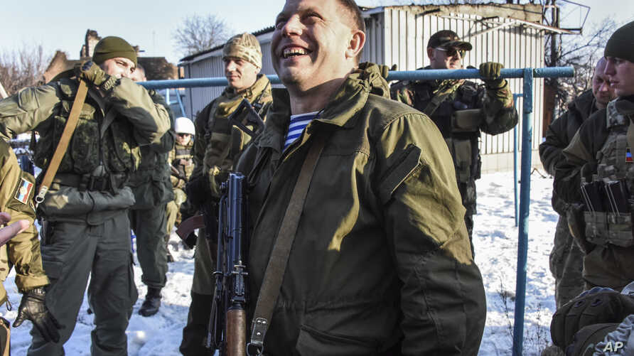 Pro-Russian rebel leader Alexander Zakharchenko, center, surrounded by guards, smiles not far from rebel positions near the Donetsk airport in Donetsk, Eastern Ukraine, Jan. 15, 2015.