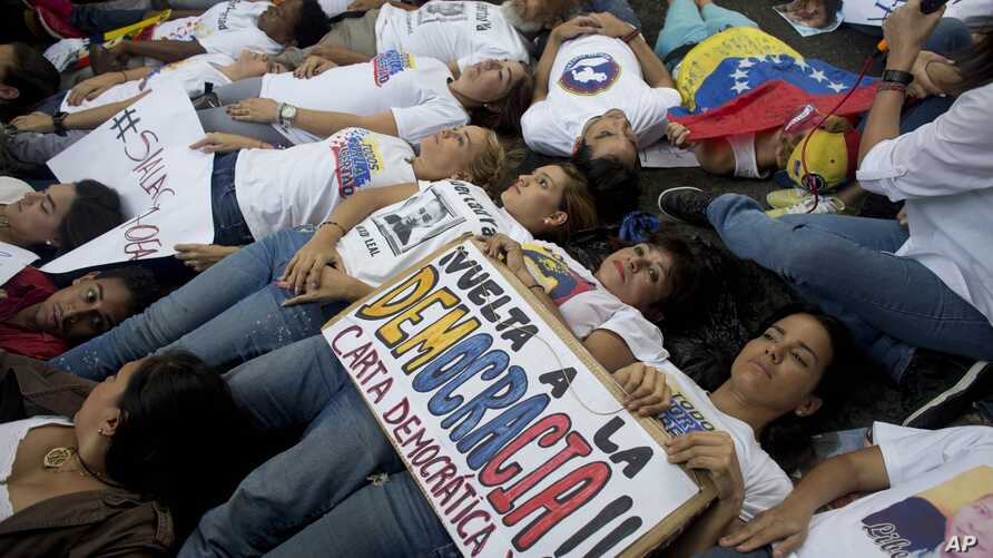 Opposition supporters lie on the ground during a demonstration outside of the Organization of American States, OAS, office building, in Caracas, Venezuela, June 23, 2016.