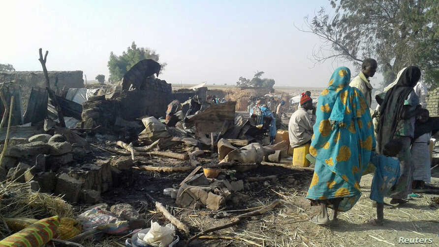 People walk at the site after a bombing attack of an internally displaced persons camp in Rann, Nigeria, Jan. 17, 2017.