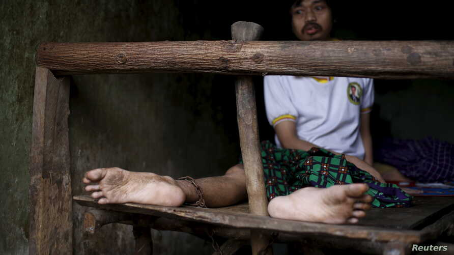 A man suffering from mental illness sits chained on a bed in his room inside his family home in Curug Sulanjana village in Serang, Banten province, Indonesia, March 23, 2016.