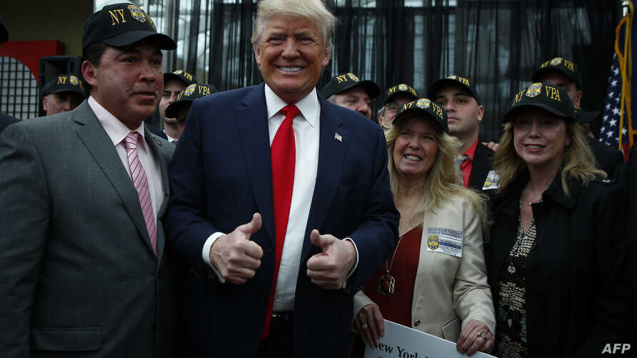 Republican presidential candidate Donald Trump poses for a picture with supporters at the end of a press conference with members of the New York Veteran Police Association in Staten Island, New York.