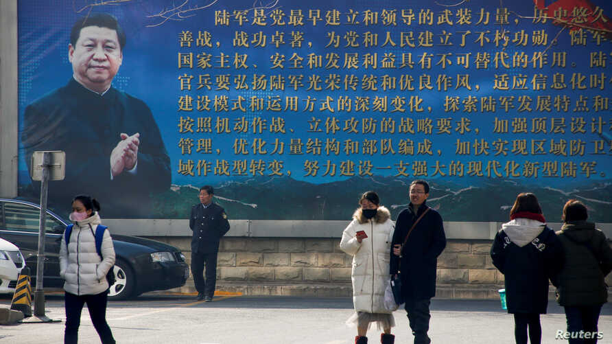 People walk in front of a poster showing a portrait of Chinese President Xi Jinping in Beijing, China, Feb. 26, 2018.