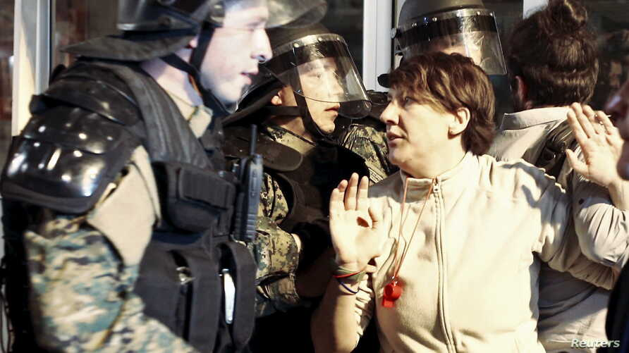 A protester clashs with policemen in front of ruling party VMRO headquarters in Skopje, Macedonia, April 12, 2016.