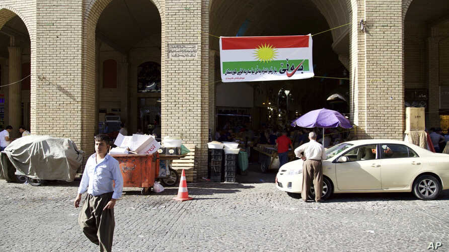 """FILE - A man walks past a campaign slogan printed on a Kurdish flag urging people to vote """"yes"""" in the upcoming poll on independence from Iraq, in Irbil, Iraq, Aug. 24, 2017."""