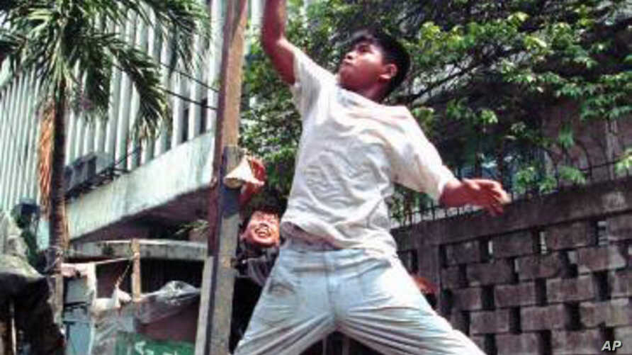 A Filipino street kid imitates a Michael Jordan slam dunk as they play their own kind of basketball at a back street in Manila.