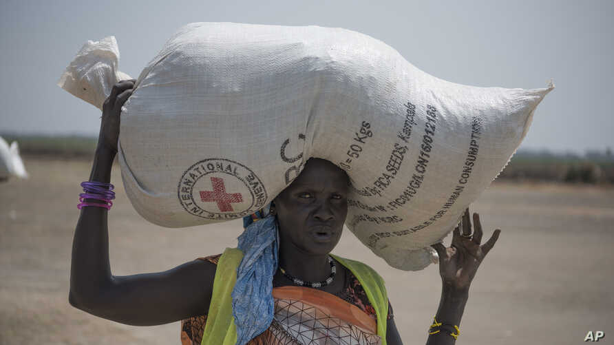 In this photo taken April 11, 2017, a woman walks back to her home after receiving food distributed by the Red Cross in South Sudan.