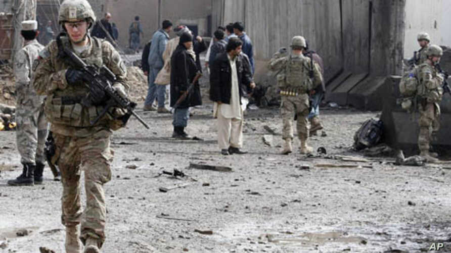 U.S. soldiers and Afghan policemen keep watch after a car bomb blast in the southern city of Kandahar, Afghanistan, February 20, 2012.
