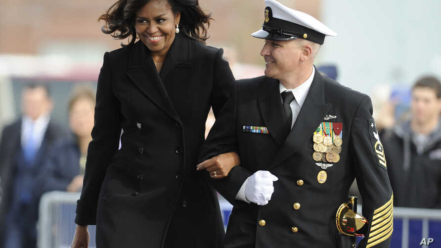 First lady Michelle Obama is escorted by USS Illinois Chief of the Boat, Master Chief David DiPietro during a commissioning ceremony for the U.S. Navy attack submarine USS Illinois, in Groton, Conn., Oct. 29, 2016. The submarine is named for Obama's